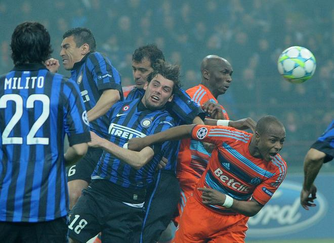 Inter Milan's Serbian midfielder Dejan Stankovic (C) fights for the ball with Marseille's Ghanean forward Andre Ayew (R) during their second leg Champions League round of 16 football match in Milan's San Siro Stadium on March 13, 2012.  AFP PHOTO / OLIVIER MORIN
