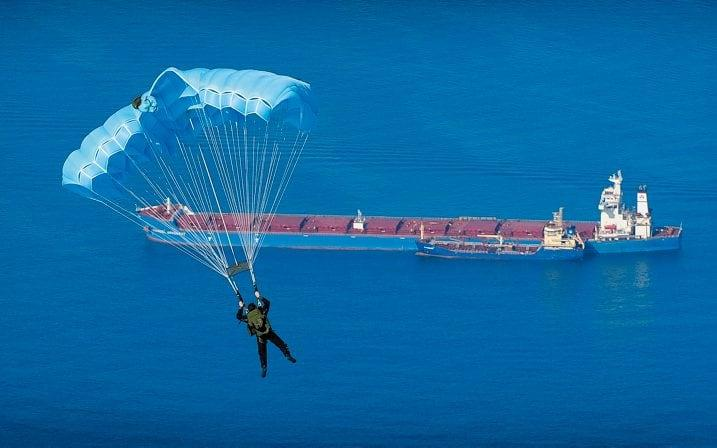 A member of the Submarine Parachute Assistance Group (SPAG) jumps into the bay of Gibraltar during an annual training exercise. - Crown Copyright