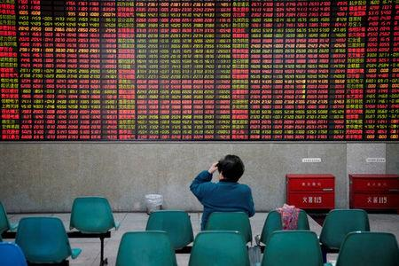 FILE PHOTO - An investor looks at an electronic board showing stock information at a brokerage house in Shanghai, China November 24, 2017. REUTERS/Aly Song