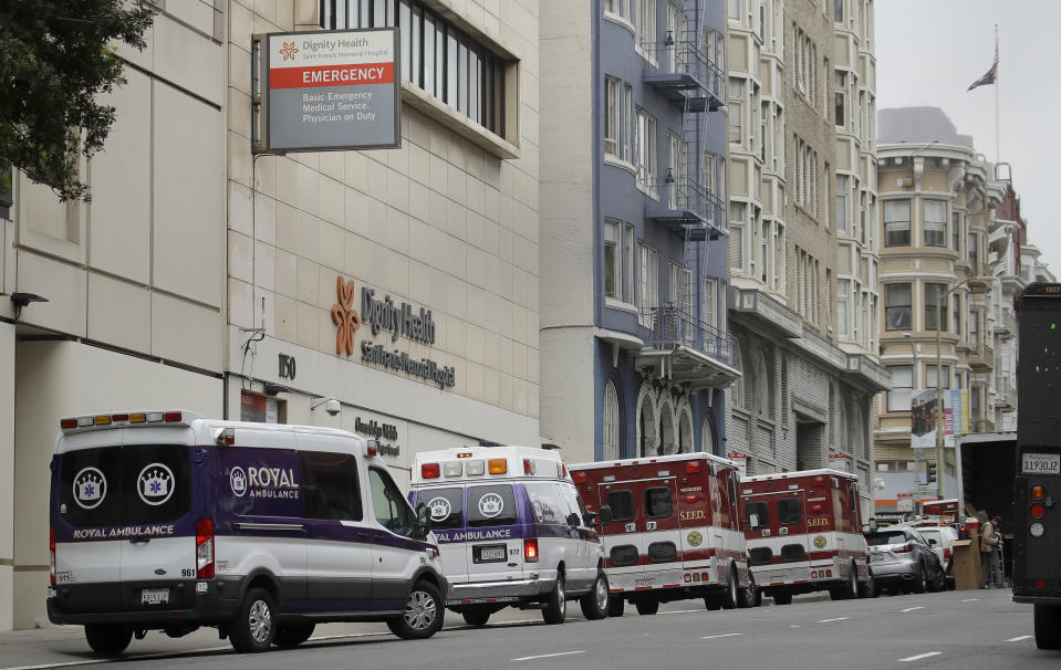 FILE - In this March 18, 2020 file photo Ambulances park in front of Saint Francis Memorial Hospital in San Francisco. After months spent tamping down surges and keeping the coronavirus at manageable levels, a variety of factors combined to bring California to a crisis point in the pandemic. (AP Photo/Ben Margot,File)
