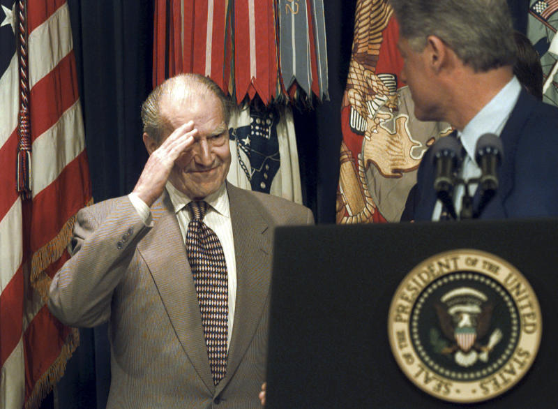 FILE - In this May 28, 1996 file photo, retired Admiral Elmo Zumwalt Jr., salutes President Bill Clinton, during a ceremony at the White House in Washington, after the president announced expanded benefits to veterans suffering side effects from exposure to Agent Orange during the Vietnam War. Zumwalt lost a son who died from diseases related to Agent Orange and was an avid supporter of increased benefits for veterans. A Navy destroyer bearing Zumwalt's name will be christened by his two daughters during a ceremony Saturday, April 12, 2014 at Bath, Maine. (AP Photo/Greg Gibson, File)