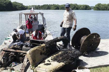 """Volunteers bring to shore garbage they collected during the second """"mega cleanup"""" of the San Juan estuary system, in San Juan October 26, 2013. REUTERS/Alvin Baez"""