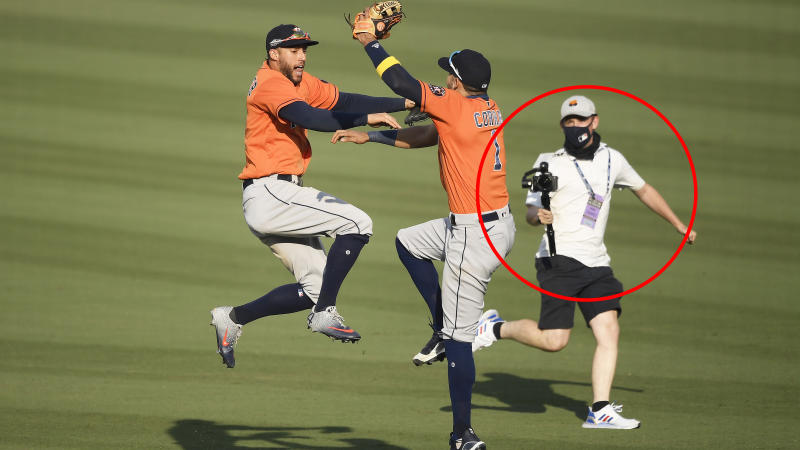An MLB employee is pictured behind Houston Astros players Carlos Correa and George Springer.