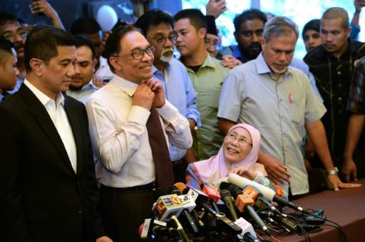 Anwar removes his tie before speaking to the media as his wife Wan Azizah (bottom R) looks on