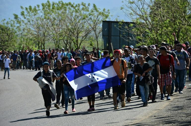Honduran migrants walk behind a Honduran national flag heading to Puerto Barrios in Guatemala, after breaking through the country's southern border with Honduras