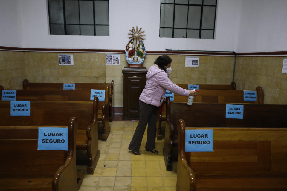 A parishioner sprays disinfectant on pews, marked with signs to encourage social distancing, ahead of Mass in a provisional chapel adjacent to the Nuestra Senora de Los Angeles, or Our Lady of Angels church, which is in the early stages of reconstruction three years after an earthquake collapsed almost half of its 18th-century cupola in Mexico City, Sunday, Oct. 4, 2020. The $2 million restoration effort here will take at least two years more; impatient residents often ask experts why it is taking so long. (AP Photo/Rebecca Blackwell)