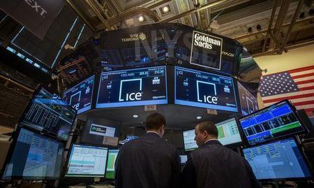 Traders work at the Goldman Sachs post that trades IntercontinentalExchange on the floor of the New York Stock Exchange, November 18, 2013. REUTERS/Brendan McDermid
