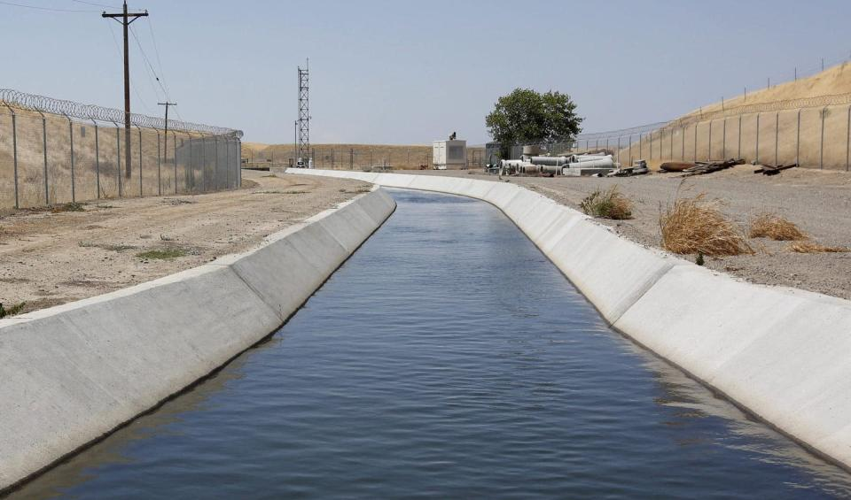 A concrete lined canal running through a dry landsacpe.