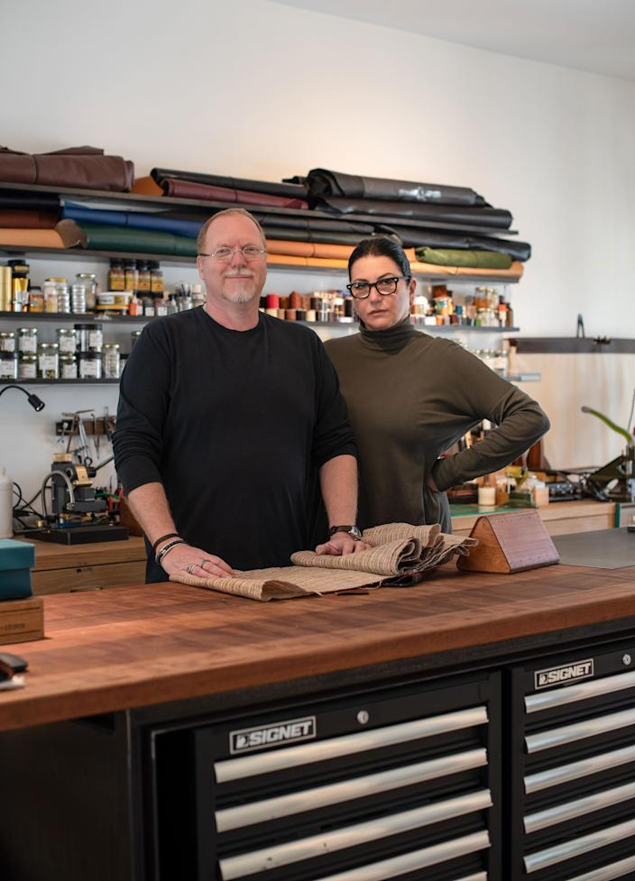 The couple pictured in Pollak's leather-working studio. Oak shelves and cabinets were crafted by a local carpenter.
