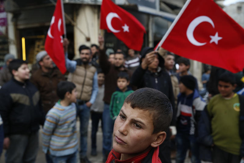 FILE - In this Jan. 27, 2018 file photo, youths wave Turkish flags as they gather in the streets of the Turkish-controlled northwestern city of Azaz, Syria. Turkey is growing long-term roots in its northern Syrian enclave, nearly two years after its troops moved in, modeling the zone on its own towns and bringing in its own administrators and military, financial and security institutions. Turkey aims to keep out its nemesis, the U.S.-backed Syrian Kurdish militia known as the YPG. (AP Photo/Lefteris Pitarakis, File)