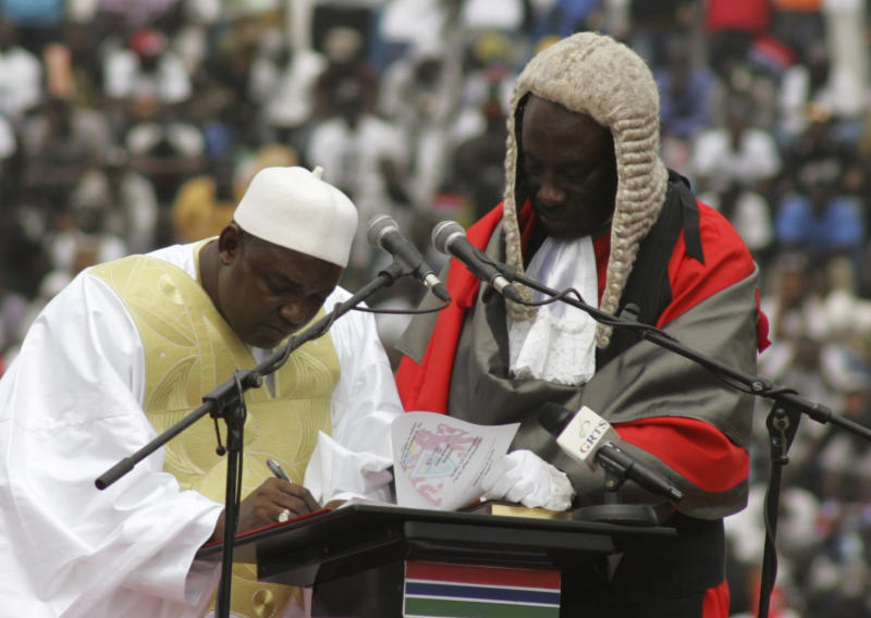 In this photo taken on Saturday, Feb. 18, 2017, Gambia President Adama Barrow, left, signs a document during his inauguration ceremony in Banjul, Gambia. As Gambia enters a new era of democracy, President Adama Barrow has reiterated his commitment to ending human rights abuses in the country. (AP Photo/Kuku Marong)