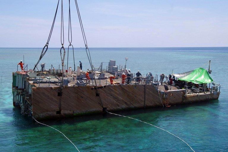 This handout photo released on March 30, 2013 by Philippine Coast Guard (PCG) shows a portion of the stern of the USS Guardian being lifted by a boat crane during a salvage operation at Tubbataha reef, in Palawan island, western Philippines