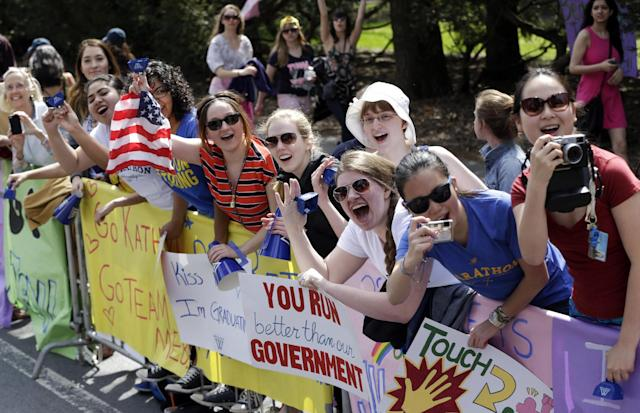 Women display placards and cheer near Wellesley College along the route of the 118th Boston Marathon, Monday, April 21, 2014, in Wellesley, Mass. (AP Photo/Steven Senne)