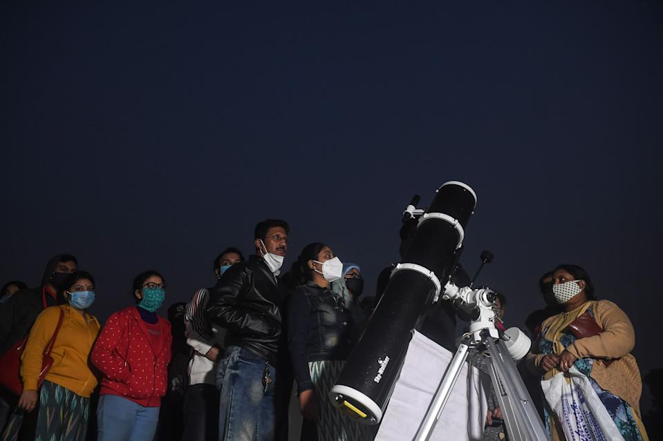 People stand in a queue to see a 'great conjunction' of Jupiter and Saturn at the Maidan area in Kolkata on December 21, 2020. (Photo by Dibyangshu SARKAR / AFP) (Photo by DIBYANGSHU SARKAR/AFP via Getty Images)