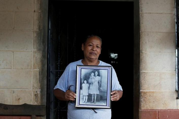 Miriam Marquez holds a picture of her mother in law killed by Salvadorean soldiers in the village of El Mozote, in the town of Meanguera