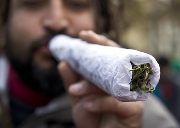 A man holds a giant joint during a march for the legalization of cannabis in Santiago, Chile (AFP Photo/Martin Bernetti)