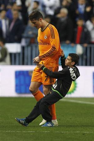 Real Madrid's Cristiano Ronaldo is grabbed by a boy as he leaves the pitch after their Spanish First Division soccer match against Malaga at La Rosaleda stadium in Malaga March 15, 2014. REUTERS/Jon Nazca