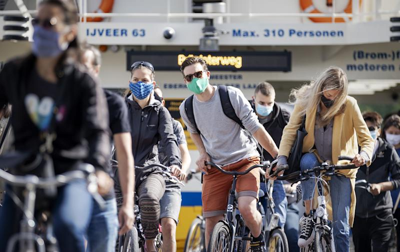 Travelers with face masks ride bicycles at the Amsterdam Central Station, The Netherlands, on June 01, 2020. Passengers on public transport must wear a face mask from 1 June to prevent the spread of the coronavirus. (Photo by Robin VAN LONKHUIJSEN / ANP / AFP) / Netherlands OUT (Photo by ROBIN VAN LONKHUIJSEN/ANP/AFP via Getty Images)