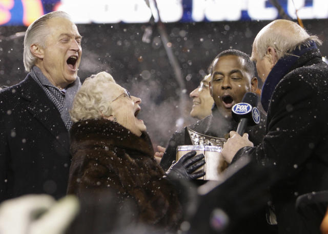 FILE - In this Jan. 21, 2007, file photo, Chicago Bears owner Virginia McCaskey and Chairman of the Board Michael McCaskey, left, react as they are presented with the George S. Halas Trophy after the Bears' 39-14 NFL football win over the New Orleans Saints to win the NFC championship football game, in Chicago. Making the presentation are Fox broadcasters Tony Dorsett and Terry Bradshaw, right. Michael McCaskey, who led the Chicago Bears for nearly three decades following the death of his grandfather George Halas, died Saturday, May 16, 2020, after a lengthy battle with cancer, the team said. He was 76. (AP Photo/Alex Brandon, File)