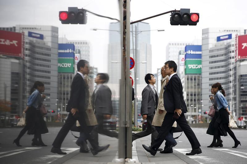People cross a street in a business district in central Tokyo