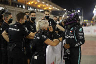 Mercedes driver Lewis Hamilton of Britain, right, celebrates with his teammates after winning the pole position after the qualifying session at the Formula One Bahrain International Circuit in Sakhir, Bahrain, Saturday, Nov. 28, 2020. (Hamad Mohammed, Pool via AP)