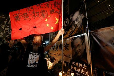 "A protester holds a defaced Chinese national flag with words ""fascist kills Liu Xiaobo"", as he mourns the death of Nobel laureate Liu Xiaobo, outside China's Liaison Office in Hong Kong, China July 15, 2017. REUTERS/Bobby Yip"