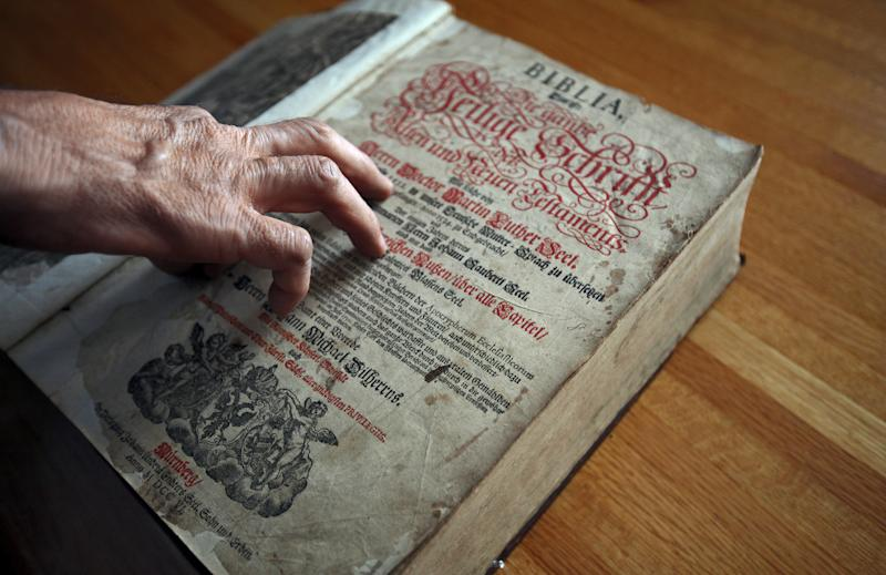 Tim Shier looks over a family bible dating from the 1700's on Feb. 3, 2013 in his home in Marysville, Ohio. The Lutheran Bible, written in German Gothic script and containing the handwritten dates of births, deaths and marriages for seven generations of Tim Shier's family, went missing in the burglary in Marysville, near Columbus, in December 2011. But thanks to a bit of luck, a sharp-eyed family member, local deputies and Goodwill, which had ended up with the Bible and then sold it online, the heirloom is back in Shier's hands. (AP Photo/The Columbus Dispatch, Chris Russell)