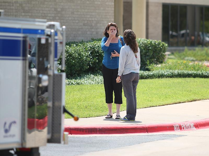A woman reacts outside of the College Station Medical Center, Monday, Aug. 13, 2012, in College Station, Texas where five victims were brought, following a shooting near the Texas A&M campus. A gunman and a law enforcement officer were among three people killed Monday in a shooting near a Texas university campus, police said. (AP Photo/Houston Chronicle, Karen Warren)