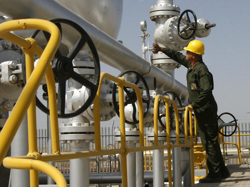 FILE- In this Tuesday, April 15, 2008 file photo, Iranian oil technician Majid Afshari checks the oil separator facilities in Azadegan oil field, near Ahvaz, Iran. When Iran welcomes leaders to a world gathering next week, few will get a grander reception than India's prime minister. As Tehran tries to offset the squeeze from Western oil sanctions, there is no greater priority than courting energy-hungry Asian markets. (AP Photo/Vahid Salemi, File)