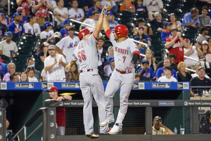 Cincinnati Reds' Eugenio Suarez (7) celebrates his three-run home run with third base coach J.R. House as he runs the bases in the fourth inning of the baseball game against the New York Mets, Saturday, July 31, 2021, in New York. (AP Photo/Mary Altaffer)