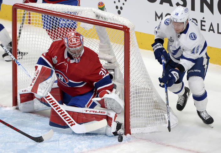 Montreal Canadiens' goaltender Carey Price (31) watches the puck as Tampa Bay Lightning's Ondrej Palat (18) chases during the first period of Game 4 of the NHL hockey Stanley Cup final in Montreal, Monday, July 5, 2021. (Ryan Remiorz/The Canadian Press via AP)