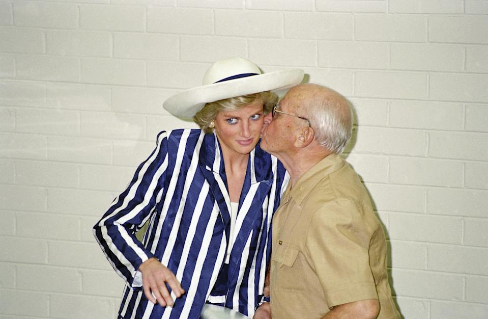 The Prof. of Music at Melbourne University, Prof. Henri Touzeau gives the Princess of Wales a kiss after she played the piano on a tour of the Victorian College of the Arts in Melbourne, Australia on Thursday, Jan. 28, 1988. She is wearing a black and white striped dress by Roland Klein.