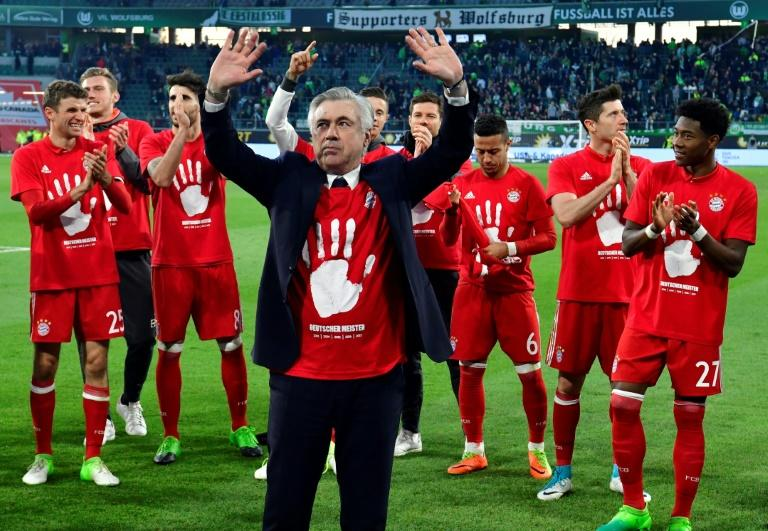 Bayern Munich's coach Carlo Ancelotti (C) and his team celebrate becoming the new German champion on April 29, 2017 in Wolfsburg, northern Germany