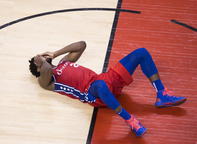 Philadelphia 76ers center Joel Embiid (21) lays on the court hurt during second half NBA Eastern Conference basketball semifinal action against the Toronto Raptors, in Toronto on Sunday, May 12, 2019. (Nathan Denette/The Canadian Press via AP)