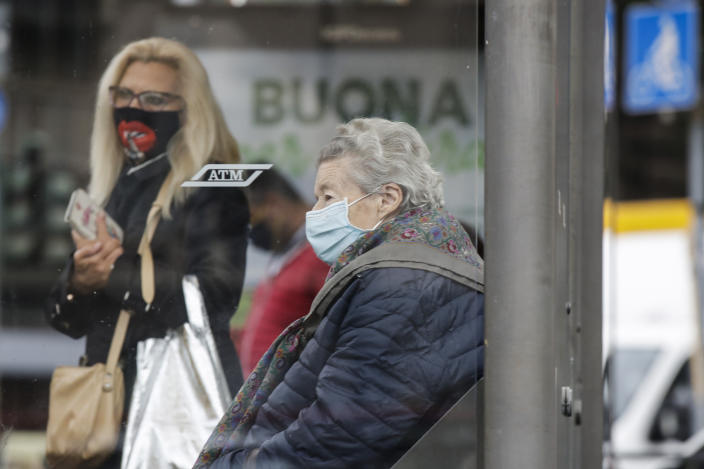 People wear face masks to prevent the spread of COVID-19 as they wait at a bus stop, in Milan, Italy, Wednesday, Oct. 14, 2020. Italian Premier Giuseppe Conte says the aim of Italy's new anti-virus restrictions limiting nightlife and socializing is to head off another generalized lockdown. (AP Photo/Luca Bruno)
