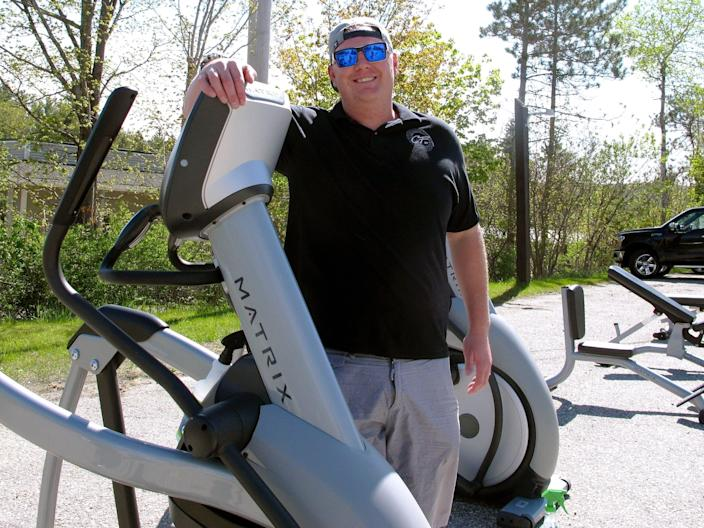 Sean Manovill, owner of Club Fitness of Vermont, poses with exercise equipment he moved outside so the Rutland, Vt., gym could reopen on May 19, 2020