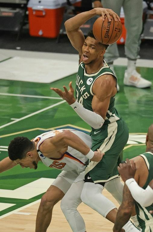Milwaukee's Giannis Antetokounmpo tries to control the ball over Phoenix's Devin Booker, left, in the NBA Finals
