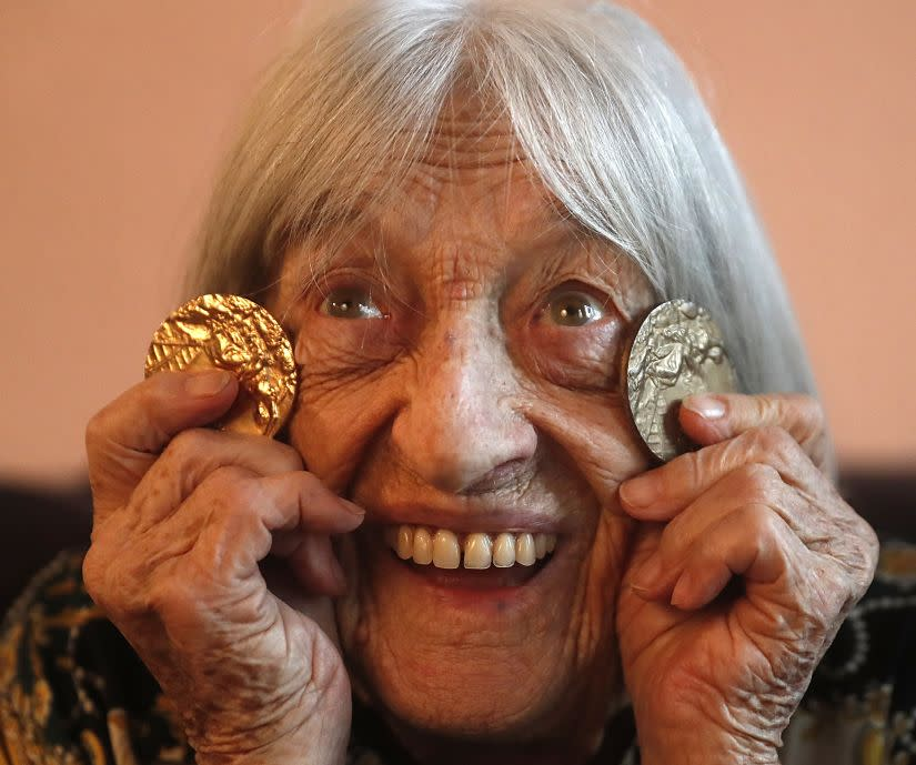 Agnes Keleti, former Olympic gold medal winning gymnast, poses for a photo with two of her Olympic medals at her apartment in Budapest. AP Photo