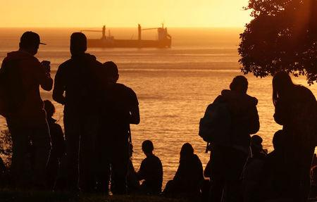 People look out towards the ocean on Cerro Castillo hill, after a mass evacuation of the entire coastline during a tsunami alert after a magnitude 7.1 earthquake hit off the coast in Vina del Mar