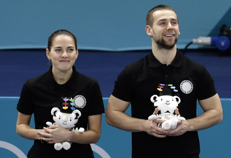 Alexander Krushelnitsky (right) won the mixed-doubles curling bronze medal with his wife Anastasia Bryzgalova. (AP)