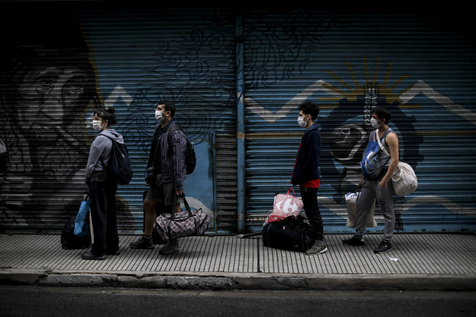 People line up to get their temperature checked before being allowed into a bus to return to their provinces in Buenos Aires, Argentina, Wednesday, April 1, 2020. The Argentine government ordered a forced lock down to help contain the spread of the new coronavirus. (AP Photo/Natacha Pisarenko)
