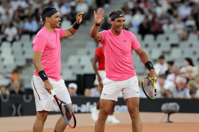 Trevor Noah and Rafael Nadal high five after winning a point against Roger Federer and Bill Gate in the exhibition match held at the Cape Town Stadium in Cape Town, South Africa, Friday Feb. 7, 2020. (AP Photo/Halden Krog)