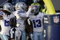 Dallas Cowboys wide receiver Michael Gallup (13) celebrates with quarterback Andy Dalton, center, and others after catching a touchdown pass in the first half of an NFL football game against the Philadelphia Eagles in Arlington, Texas, Sunday, Dec. 27. 2020. (AP Photo/Ron Jenkins)