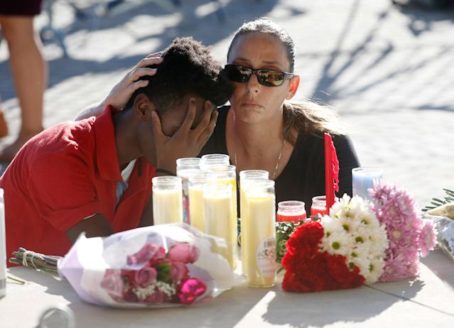 <p>Pamela Tilton, right, comforts Che James-Riley, 18, as they light a candle at a memorial for the victims of the shooting at Marjory Stoneman Douglas High School, Thursday, Feb. 15, 2018, in Parkland, Fla. Tilton, a swimming coach and swimmer James-Riley at Coral Lakes High School, competed against one of the victims. (Photo: Wilfredo Lee/AP) </p>