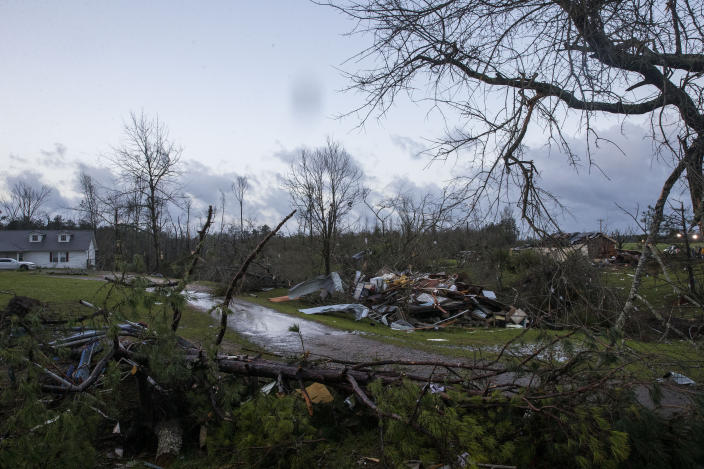 The sun rises over weather-damaged properties in Clanton, Ala., the morning following a large outbreak of severe storms across the southeast, Thursday, March 18, 2021. (AP Photo/Vasha Hunt)
