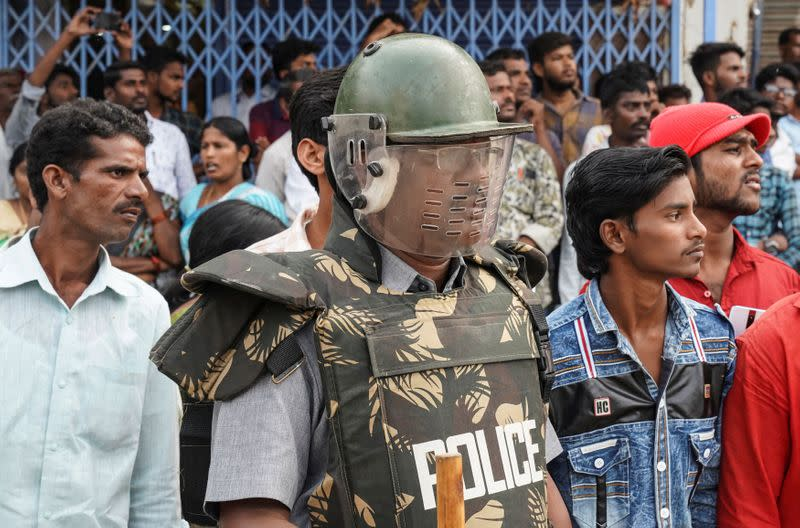 A police officer stands guard as people attend a protest against the alleged rape and murder of a 27-year-old woman in Shadnagar