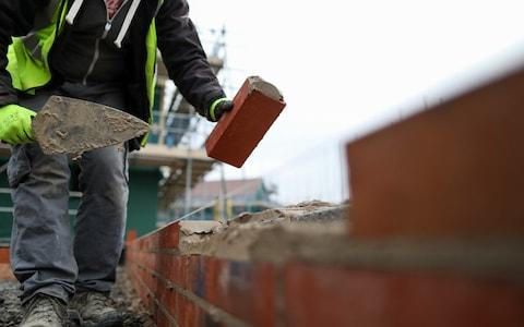 <span>A builder lays bricks at a property development (stock photo)</span> <span>Credit: Chris Ratcliffe/Bloomberg </span>