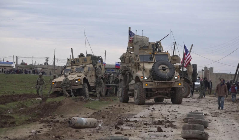 In this frame grab from video, people and soldiers gather next to an American military convoy stuck in the village of Khirbet Ammu, east of Qamishli city, Syria, Wednesday, Feb. 12, 2020. The Syrian official news agency SANA, said Wednesday, that locals had gathered at an army checkpoint, pelting the U.S. convoy with stones and taking down a U.S. flag flying on a vehicle when troops fired with live ammunition and smoke bombs. (AP Photo)