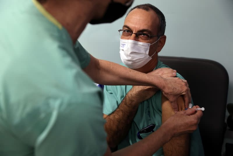 Doctor Guy Choshen, director of the COVID-19 ward in Ichilov Hospital, gets his second vaccination injection against coronavirus disease in Tel Aviv