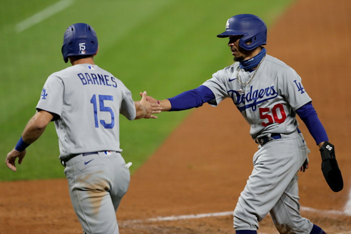 """Dodgers catcher Austin Barnes, left, and right fielder Mookie Betts celebrate after scoring on a single by Chris Taylor during the fifth inning. <span class=""""copyright"""">(Matthew Stockman / Getty Images)</span>"""